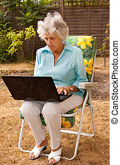 Mature Lady Working On A Laptop - An elderly woman using a...