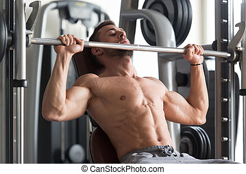 Exercising Shoulders With Barbell - Muscular Man Doing Heavy...