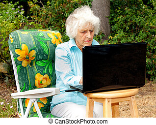 Working The Web - An elderly woman using a laptop computer...