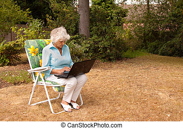 Wireless Connection - An elderly woman using a laptop...