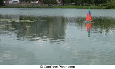 small boat-sailboat on the radio swims in the lake.