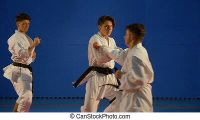 Young men fighting in karate competition in slow motion