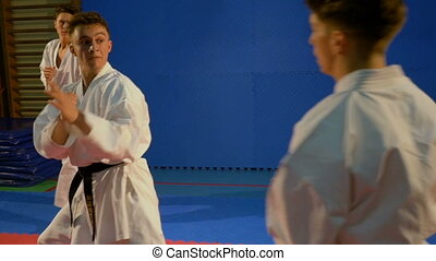 Three teenagers practicing karate and engaging in combat...