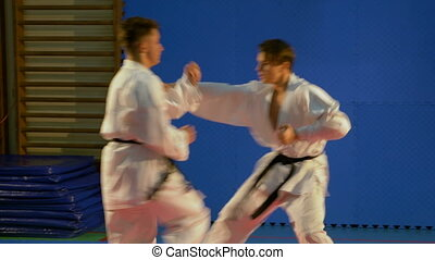 Young men in kimono with black belt practicing self defense...