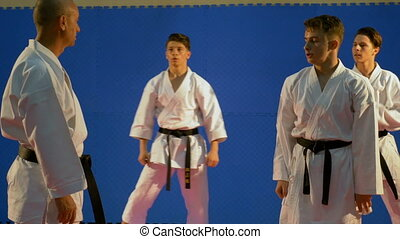 Sensei karate teacher talking with his team of students in dojo during training for competition