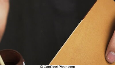 Painting leather edge. - Closeup view of craftsman's hands...
