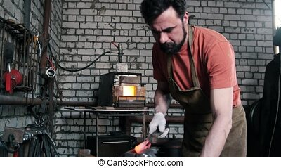 In the forge, the man inserts the detail in the vise - In...