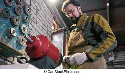 The smith sharpens the steel detail - Blacksmith in...