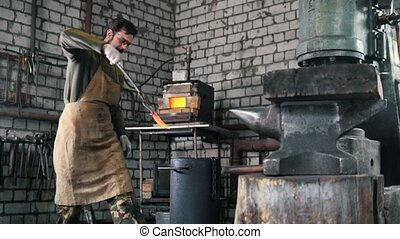Blacksmith chills the detail in a barrel of engine oil -...