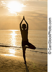 Yoga guy silhouette, working on poses at sunset
