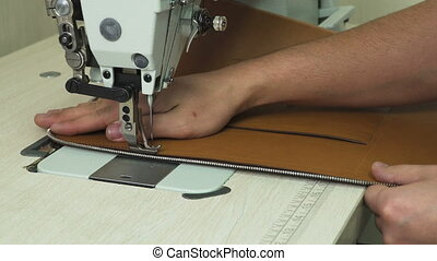 stitching leather product with modern sewing machine. -...