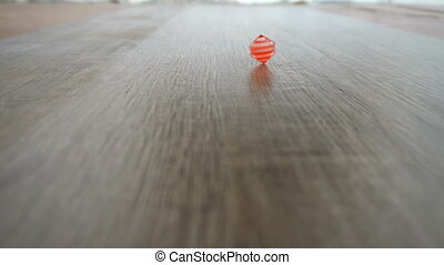male hand spinning red cube on grey laminate slow motion.