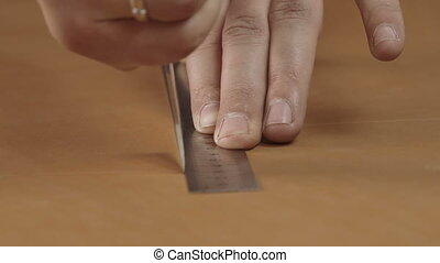 Cutting a piece of leather - Craftsman's hands cutting a...