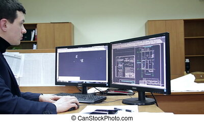 man making blueprints on computer. with two monitors.