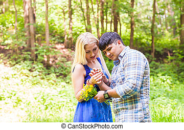 butterfly on woman and man hands in nature