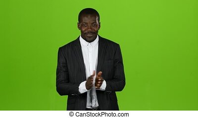 Black african american guy claps his hands and smiles. Green...