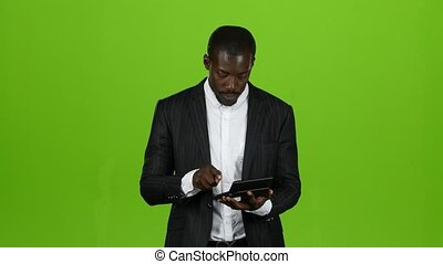 African businessman calculates his income on a calculator, he smiles. Green screen