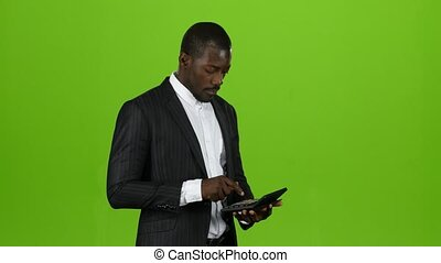 African businessman is standing and counting his income on the calculator, he likes to get a huge come, shows a thumbs up. Green Screen