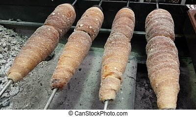 Rotisserie of buns on some metal spits in an open oven in some street in Europe