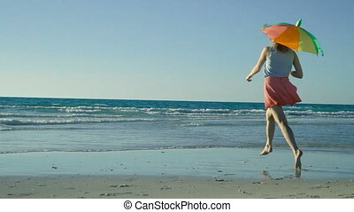 Happy girl runs and jumps on beach, plays with colored umbrella. Funny woman having fun in sea, waited vacation to long. Slender beautiful legs running on sand. Hipster with pink glasses going crazy