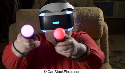 Elderly woman in VR headset uses move motion controller for...