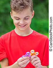 Teen boy with spinner toy in park