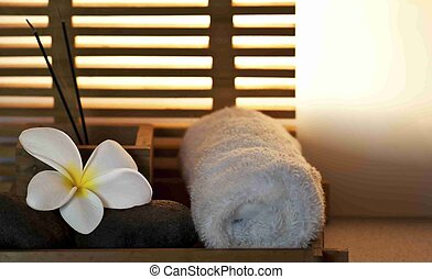tranquil spa setting with flower, stones, incense and towel