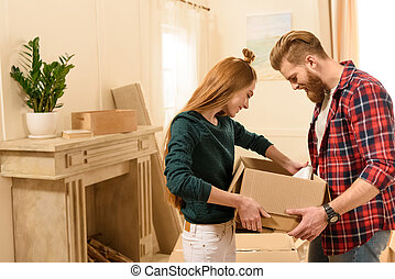 side view of young smiling couple looking into cardboard box at new home