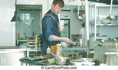 Chef of the restaurant prepares dishes in the kitchen. 4k -...