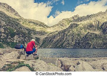 Trekker enjoying crystal clear water. Lake Lambien in Brenta...