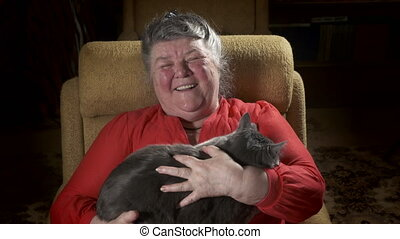 Elderly woman in an armchair stroking her cat.