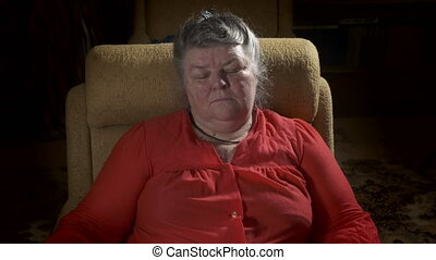 An elderly fat woman sits in armchair watching TV in a dark...