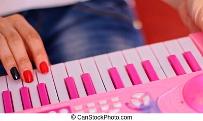 Closeup Woman Fingers Play Pink Toy Keyboard Piano - closeup...
