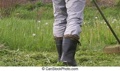 A man mowing the grass in the garden closeup - A man mowing...