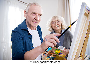Smiling senior woman looking at husband painting picture