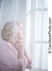 Pensive senior woman looking out of the window, veil in front