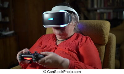 Elderly woman in front of TV screen uses VR headset and...