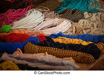Ropes of different colors and diameters on the market counter. India