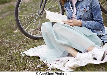 Low section of woman which reading a book outside