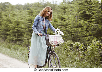 Happy woman with bike at the park