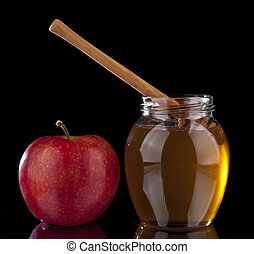 honey and red Apple on black background