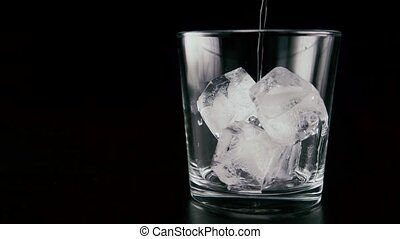 Pour vodka into the ice. Slow mo - In a glass with ice pour...