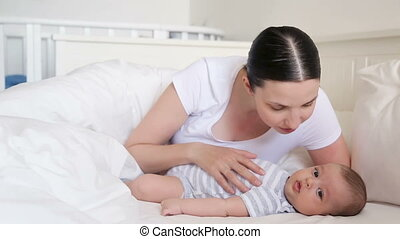 mom lies in bed with a newborn who yawns and trifling with...