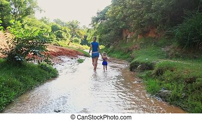 Mother and Daughter Walk in Shallow Stream against Sun Beams...