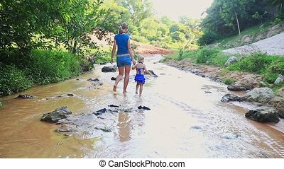 Mother with Daughter Walk along Shallow River
