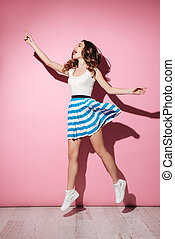 Full length portrait of a pretty girl in dress jumping