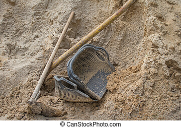 Hoe and basket on sand
