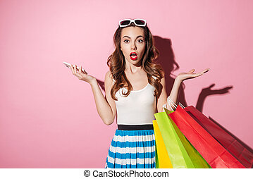 Pretty shocked girl holding shopping bags and mobile phone -...