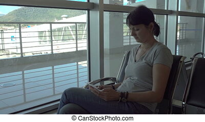 Woman checks her ticket in the airport waiting area. - Woman...