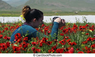 Girl is Photographing Field of Flowering Poppies in the...